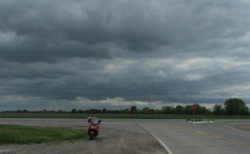 Motor scooter at crossroads under storm clouds.